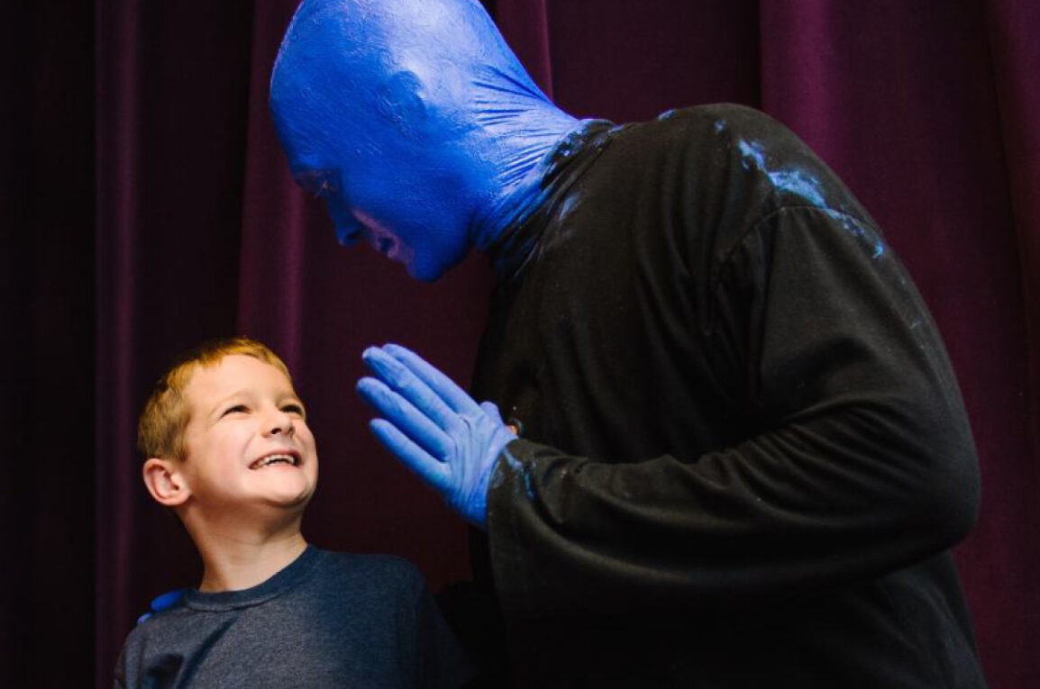 Blue Man Group member presents to a young boy with huge smile.